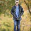 Man Walking Through Autumn Park Listening to MP3 Player