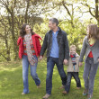 Young Family Outdoors Walking Through Park — Stok fotoğraf