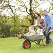 Parents Giving Children Ride In Wheelbarrow - Stock Photo