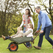 Stock Photo: Parents Giving Children Ride In Wheelbarrow