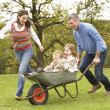 Parents Giving Children Ride In Wheelbarrow — Stock Photo