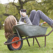 Young Girl Laying Wheelbarrow Using Smart Mobile Phone — Stock Photo