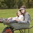Two Sisters Sitting In Wheelbarrow Outdoors - Stock Photo