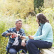 Foto Stock: Couple Enjoying Picnic Outdoors In Autumn Woodland