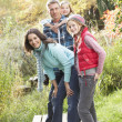 Stockfoto: Family Group Standing Outdoors On Wooden Walkway In Autumn Lands