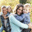 Family Group Outdoors In Autumn Landscape With Parents Giving Ch — Stock Photo