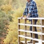 Man Standing On Wooden Balcony Overlooking Autumn Woodland — Stock Photo