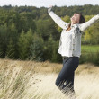 Young Woman Enjoying Freedom Outdoors in Autumn Landscape - Lizenzfreies Foto