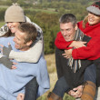 Two Couples Having Piggyback Ride In Autumn Landscape — Stock Photo