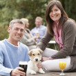 Couple With Pet Dog Outdoors Enjoying Drink In Pub Garden — Stock Photo