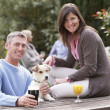 Foto de Stock  : Couple With Pet Dog Outdoors Enjoying Drink In Pub Garden