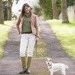 Woman Taking Dog For Walk Outdoors In Autumn Park — Stock Photo