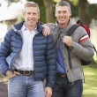 Two Male Friends Walking Outdoors In Autumn Park Together — Stock Photo #4836510