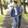 Two Male Friends Walking Dog Outdoors In Autumn Park Together — Stock Photo