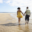 Stock Photo: Romantic Young Couple Walking Along Shoreline Of Beach Holding H