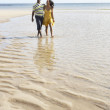 Romantic Young Couple Walking Along Shoreline Of Beach Holding H — Stock Photo