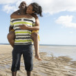 Royalty-Free Stock Photo: Young Man Giving Woman Piggyback Along Shoreline Of Beach
