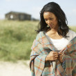 Thoughtful Young Woman Standing On Beach Wrapped In Blanket - Stok fotoraf