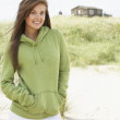 Young Woman Standing On Beach Wearing Hooded Top With Old Beach — Stock Photo