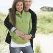 Romantic Young Couple Standing By Dunes With Beach Hut In Distan — Stock Photo #4836702
