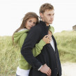 Romantic Young Couple Standing By Dunes With Beach Hut In Distan - Stock Photo