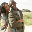 Romantic Young Couple Standing By Dunes With Beach Hut In Distan — Stock Photo