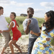 Stock Photo: Group Of Young Having Fun Dancing On Beach Together