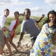 Group Of Young Having Fun Dancing On Beach Together - Stock Photo