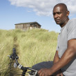 young man riding mountain bike by dunes with old beach hut in di — Stock Photo