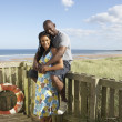 Romantic Young Couple Standing By Wooden Fence Of Beach Hut Amon — Stock Photo