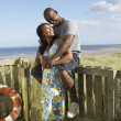 Stock Photo: Romantic Young Couple Standing By Wooden Fence Of Beach Hut Amon