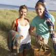 Young Couple Carrying Picnic Basket And Windbreak Walking Throug — Stock Photo