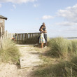 Romantic Young Couple Standing By Wooden Fence Of Beach Hut Amon - Stock Photo