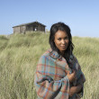 Young Woman Standing On Beach Wrapped In Blanket With Beach Hut - 图库照片