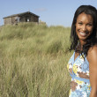 Young Woman Standing On Beach Amongst Dunes With Beach Hut In Di — Stock Photo