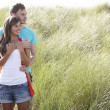Romantic Young Couple Standing Amongst Dunes — Stock Photo