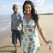 Romantic Young Couple Walking Along Shoreline Of Beach Holding H - Stock Photo