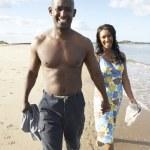 romantický mladý pár procházky podél pobřeží pláže drží h — Stock fotografie