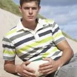 Teenage Boy Sitting On Beach Holding Rugby Ball — Stock Photo