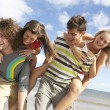 Group Of Young Friends Having Fun On Summer Beach Together - Stock Photo