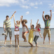Group Of Teenage Friends Having Fun On Beach Together Jumping In — Stock Photo