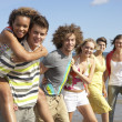 Group Of Young Friends Walking Along Summer Shoreline — Foto Stock