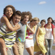 Group Of Young Friends Walking Along Summer Shoreline — Stockfoto