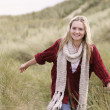 Teenage Girl Walking Through Sand Dunes Wearing Warm Clothing — Stock Photo #4836883