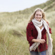 Teenage Girl Walking Through Sand Dunes Wearing Warm Clothing — Stock Photo #4836886
