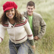 Teenage Couple Walking Through Sand Dunes Wearing Warm Clothing — Stock Photo