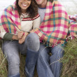 Young Couple Sitting In Sand Dunes Wrapped In Blanket
