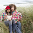 Royalty-Free Stock Photo: Young Couple Sitting In Sand Dunes Wrapped In Blanket