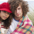Young Couple Sitting In Sand Dunes Wrapped In Blanket - 图库照片