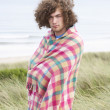 Young Man Standing In Sand Dunes Wrapped In Blanket - Stock Photo